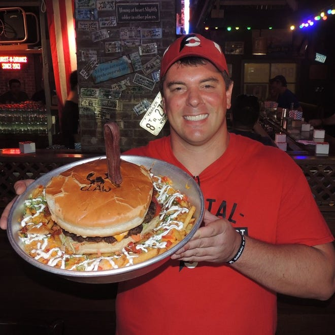 Randy Santel poses with a 5.2 pound meal consisting of a burger and loaded french fries, a food challenge he completed in May while visiting Dubai.