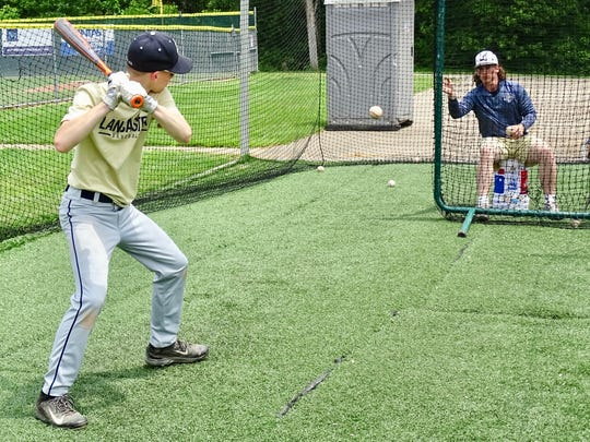 Lancaster junior baseball player Wes Ward tosses a ball to a camper in the batting cage during the Golden Gales Summer Baseball Camp.
