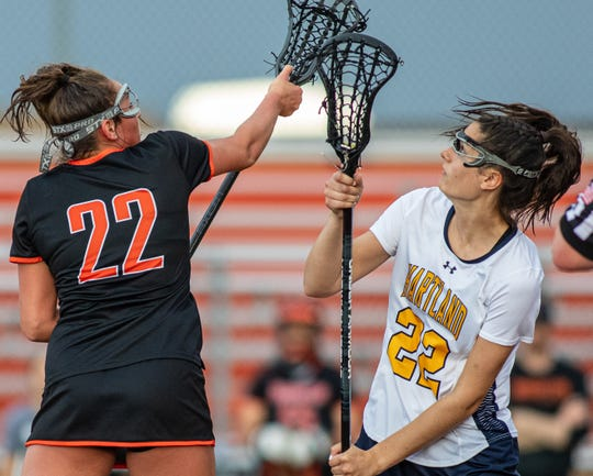 Brighton's Maddie Mince (left) and Hartland's Elena Salazar battle for the ball in a state semifinal lacrosse game on Wednesday, June 5, 2019.
