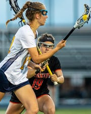 Brighton's Cat Kopchia (19) defends Hartland's Abigail Trosin in a state semifinal lacrosse game on Wednesday, June 5, 2019.