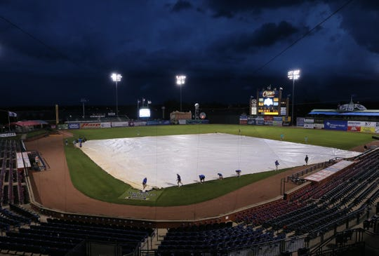 The ground crew places a tarp on the Whitaker Bank Ballpark field following a lightning delay during the Beechwood-Breckinridge County game in the KHSAA state baseball tournament.