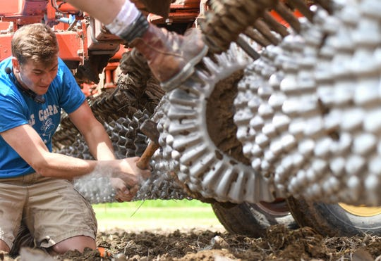 Joe Feldpausch of Pat Feldpausch Farms in Fowler, left, helps his father, Pat, remove a rock lodged in a tiller Thursday, June 6, 2019. Because of rain and wet fields, Feldpausch has only recently planted 300 acres of corn and has another 2,500 acres to plant.