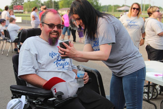 Ron Johnson, who was diagnosed with ALS in October, looks at a picture of his newly painted pink hair during a walk around Elgin's football field last Friday to raise awareness for the neurodegenerative disease.