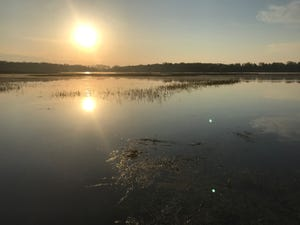 The sun rises over School Section Lake in May 2019. The water level has returned to normal, and the lake is now open to the public.