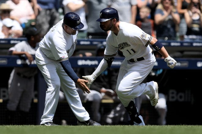 Brewers third-base coach Ed Sedar and Mike Moustakas celebrate after Moustakas hit a home run in the first inning.