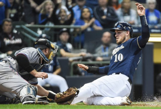 Yasmani Grandal of the Brewers is tagged out at home by Marlins catcher Bryan Holaday as he tried to score from first on Orlando Arcia's double to center in the second inning.