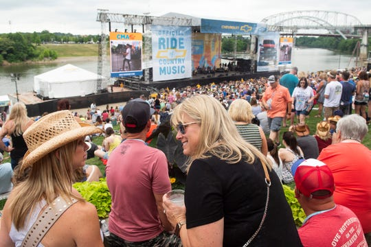 Pam Zettervall, right, and Jen Bozeman, left, chat as Billy Currington performs during the 2019 CMA Fest at Chevy Riverfront Stage in Nashville, Tenn., Thursday, June 6, 2019.