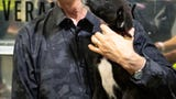 Randy Travis cuddles with adoptable puppies from Miranda Lambert's MuttNation Foundation booth at CMA Fest Fan Fair.