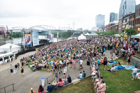 Festivalgoers take in a performance from Billy Currington at CMA Fest's Chevy Riverfront Stage on Thursday. Rain fell on downtown Nashville during the opening day of the festival, but didn't seem to be keeping the crowds away.