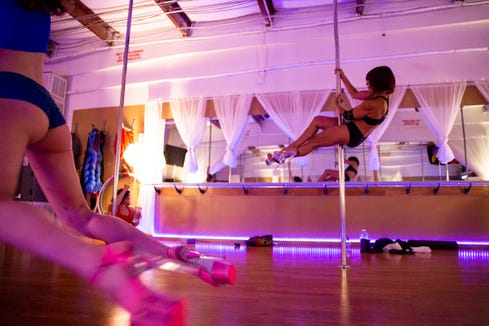 """Bebe Booskos, right, practices a pole trick at Pole & Aerial Fitness of Southwest Florida in Bonita Springs on Tuesday, May 14, 2019. """"I don't want to be old, I've never thought of myself as old,"""" said Booskos, 65."""