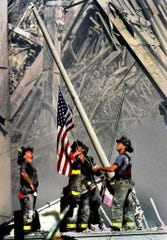 Three firefighters raise the flag on 9/11