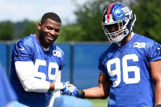 New York Giants linebackers Lorenzo Carter, left, and Kareem Martin (96) shake hands during drills on Day 3 of Giants minicamp on Thursday, June 6, 2019, in East Rutherford.