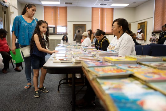 Valentina Londono, 8, browses for free books as her mother Natalia Bedoya looks on during the annual 50-Book Club celebration at Paterson Free Public Library to recognize Paterson students who read 50 books during the school year on Thursday, June 6, 2019.