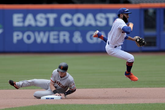 New York Mets shortstop Amed Rosario, right, leaps over San Francisco Giants' Mike Yastrzemski while trying to turn a double play on a ball hit by Pablo Sandoval during the fourth inning of a baseball game, Thursday, June 6, 2019, in New York. Sandoval beat out the throw at first base. (AP Photo/Julio Cortez)