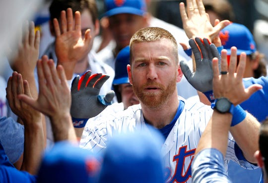 Jun 6, 2019; New York City, NY, USA;   New York Mets third baseman Todd Frazier (21) celebrates in the dugout after hitting a home run against the San Francisco Giants in the eighth inning at Citi Field. Mandatory Credit: Noah K. Murray-USA TODAY Sports