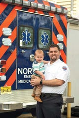 Assistant chief of Norwood's  ambulance squad Chris Barron with his 18 month old son, Christopher, photographed outside of Norwood EMS.
