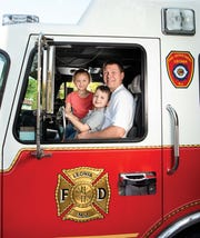 Daniel Neu, a firefighter with the Leonia Volunteer Fire Department, poses for a photo with his son Jackson Neu, 5 and daughter Maesyn Neu, 7 in Leonia.