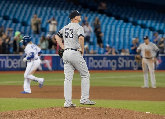 New York Yankees pitcher Zack Britton walks off the mound after giving up a three-run home run to Toronto Blue Jays Vladimir Guerrero Jr., left, during the eighth inning of a game Wednesday, June 5, 2019, in Toronto.