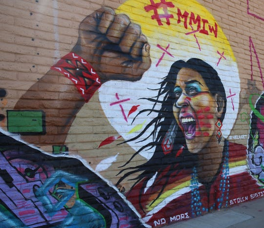 "An indigenous woman takes center stage on a wall mural at the Cruces Creatives building, with a strong message, ""NO MORE STOLEN SISTERS."" The #MMIW hash tag atop stands for Missing and Murdered Indigenous Women."