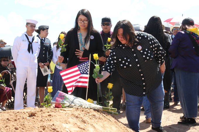 Relatives of Navajo Code Talker William Tully Brown Sr. place flowers his grave at the Fort Defiance Veterans Cemetery on June 6 in Fort Defiance, Ariz.