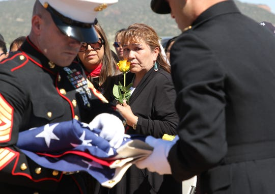 Vee F. Browne-Yellowhair, center, watches U.S. Marine Corps members fold the burial flag for her father, Navajo Code Talker William Tully Brown Sr., on June 6 at the Fort Defiance Veterans Cemetery in Fort Defiance, Ariz.