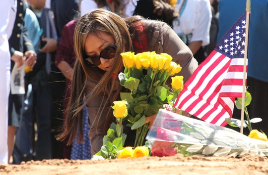 Delilah Yazzie places roses on the grave of her grandfather, Navajo Code Talker William Tully Brown Sr., on June 6 at the Fort Defiance Veterans Cemetery in Fort Defiance, Ariz.