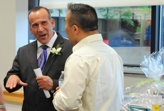 Robert Herrera, left, speaking to a community member during his introduction the district on June 5.