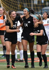 Brianna McNab, right, is congratulated for her goal by her teammates, including Kennedy White (center).