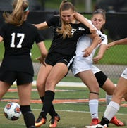 Both teams complained about a lot of holding and tackling and each were issued yellow cards during the game. Here a Wildcat is yanked back by Dearborn High defender Dayla Dakroub, right.