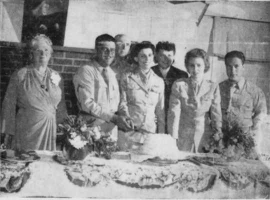 An army wedding is shown here from 1944. The Non-Commissioned Officers club cut cake for the newlywed first enlisted couple.