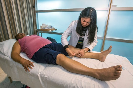 Dr. Kym Loi places acupuncture needles in the leg of Alma Garcia, 58, of Santa Ana, at UCI's Family Health Center in Santa Ana on Friday, May 10, 2019. The clinic offers acupuncture to uninsured patients and those on Medi-Cal who cannot otherwise afford these treatments. (Photo by Mark Rightmire, Orange County Register/SCNG)