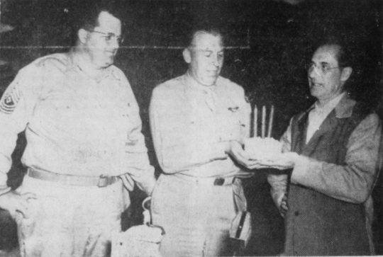 First Sergeant Burt O. Randall and Major John R. Hamilton receiving cake as a prize celebrating their win in the Groucho Marx contest in 1944.