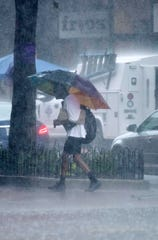 A  pedestrian navigates through the rain-soaked streets of downtown Pensacola during a downpour June 6.