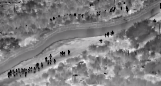 A photo taken from a video released by U.S. Customs and Border Protection shows 134 Central Americans walking around border fencing on June 4, 2019, in the small border town of Sasabe.