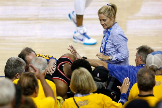 Kyle Lowry #7 of the Toronto Raptors is pushed by Warriors minority investor Mark Stevens (blue shirt) after falling into the seats after a play against the Golden State Warriors in the second half during Game Three of the 2019 NBA Finals at ORACLE Arena on June 05, 2019 in Oakland, California.