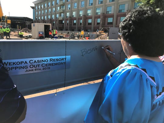 """Bernadine Burnette, president of the Fort McDowell Yavapai Nation, signs the beam as part of the """"topping out"""" ceremony to celebrate the construction progress of the new We-Ko-Pa Casino Resort, June 6, 2019."""