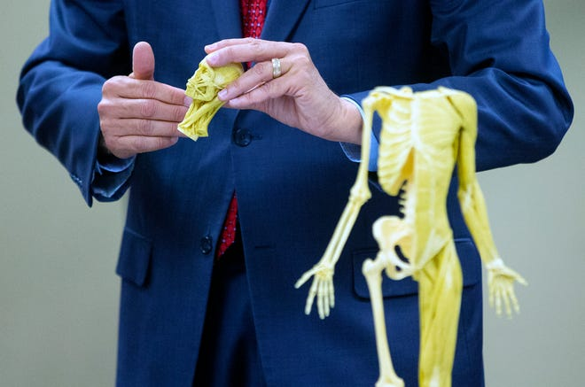 Research for Life CEO Garland Shreves uses a plastic human skeleton to explain to prospective donors how the body donation company might dissect ordismember their bodies.