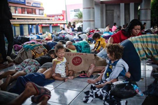 Migrantes de la caravana toman un descanso antes de seguir su camino rumbo al norte.