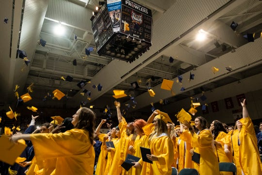 Graduating seniors from Port Huron Northern throw their caps at the end of the school's commencement ceremony Wednesday, June 5, 2019 at McMorran Arena.