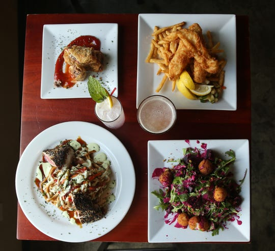 Clockwise from top left, Philly cheesesteak egg roll, Captain's Fish and Chips,  beet salad and sesame crusted ahi tuna with a Lavender Breeze cocktail and Samuel Adams Summer Ale from the Ice House House on Main Street in Poughkeepsie on June 6, 2019.