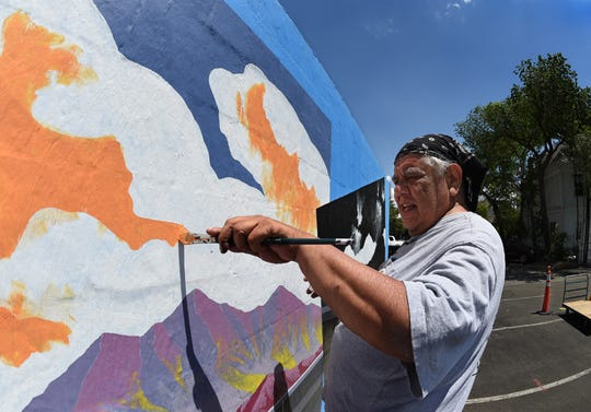 Reno artist Jack Malotte works on his mural on the back side of the Nevada Museum of Art on June 4, 2019. Malotte's  work, which will be on display in the Robert Z. Hawkins Gallery thru October 20, 2019, focuses on contemporary Native American political issues.