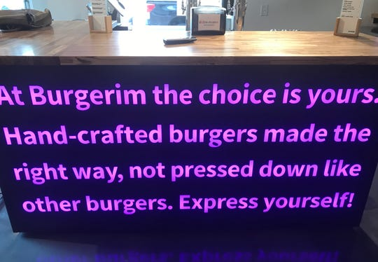 The bar at the new Burgerim in downtown Reno is faced with a glowing LED mission statement.