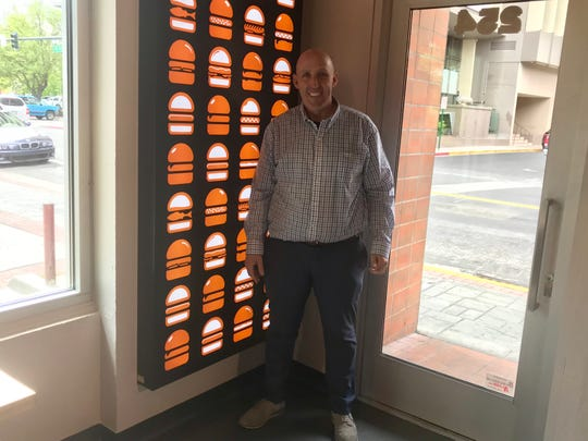 Jay Hackstaff, a longtime Northern Nevada restaurant professional, takes a moment in front of a glowing wall of  icons at Burgerim, the burger franchise he's opening in downtown Reno.