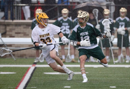 Vestal's JT Stirpe tries to work his way past Victor defender Sutton Boland.