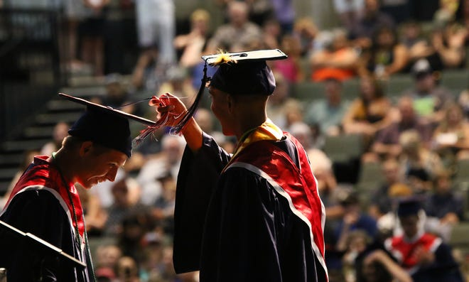 Two Central Valley High School graduates help each other to turn the tassel to the left of their caps Wednesday, June 5, 2019 after graduation at the Redding Civic Auditorium. At Central Valley's 61st commencement, 116 seniors received their diplomas. (Hung T. Vu/Special to the Record Searchlight)