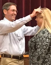 "COSST director Butch Jordan crowns Jennifer Russell as the ""queen volunteer"" at the Damon McCoy meet."
