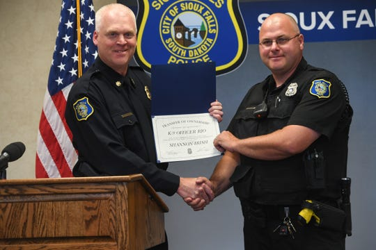 Assistant Chief Kyle Hoekstra presents Officer Shannon Irish with a transfer of ownership certificate signifying that K-9 Rio is retired from the police force Thursday, June 6, in Sioux Falls.