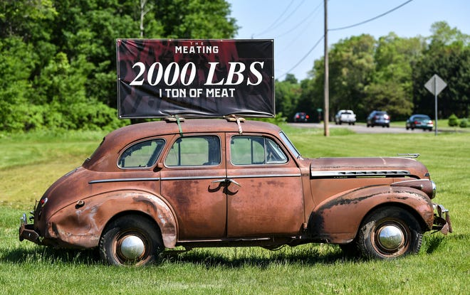 """An old car and a sign announce the upcoming """"The Meating"""" event Thursday, June 6 at The Waters Church in Sartell. The event will be held Sunday and will feature 1 ton of barbecued meat for attendees."""