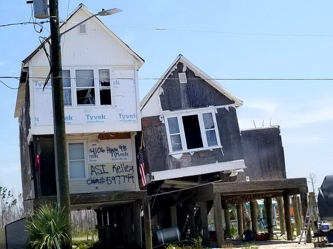 Hurricane Michael's storm surge lifted this home in Mexico Beach off the pilings, leaving it leaning precariously into the house next door.