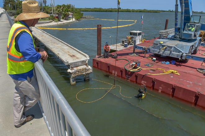"""Standing along the Wabasso Causeway bridge, James """"Chip"""" Boyette (left), project specialist engineering division for Indian River County, monitors the progress of the crew from Underwater Engineering Services Inc., of Fort Pierce, on Thursday, June 6, 2019, as diver Daniel Mattson (bottom) prepares a submerged section of the hurricane damaged Wabasso fishing pier for removal from the Indian River Lagoon. Indian River County is having all the remnants of the fishing pier damaged by Hurricane Mathew in 2016, removed, with the components of the pier becoming an artificial reef three miles offshore. """"It's good that it goes to a good environmental source that's going to nourish our fish and our coast,"""" Boyette said about the proposed reef."""